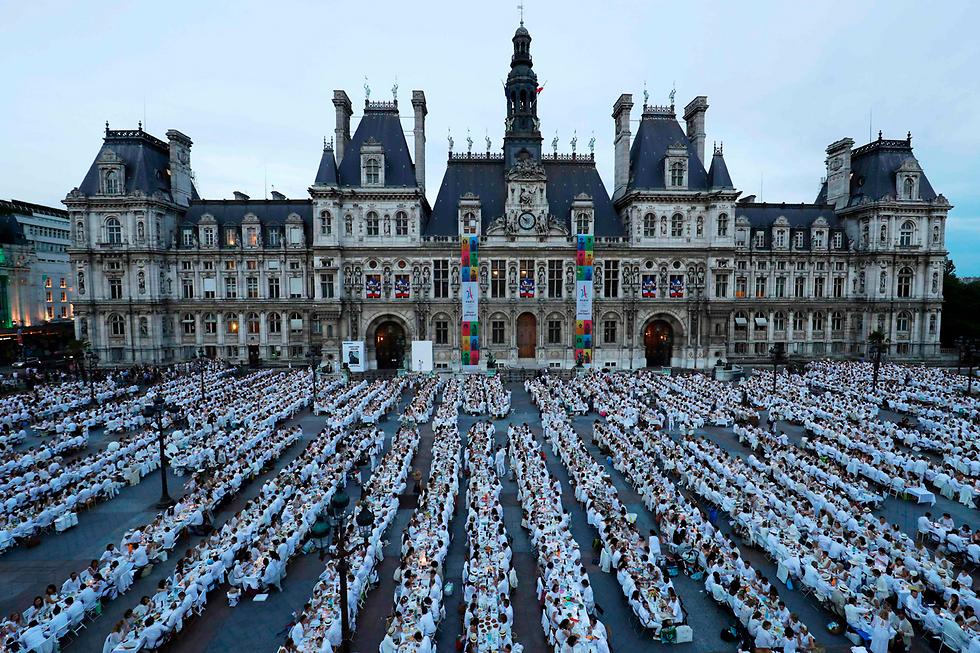 """אלפי בני אדם השתתפו ב""""ארוחת ערב בלבן"""" מול בניין עיריית פריז - אירוע שמתקיים זו השנה ה-29 (צילום: AFP)"""