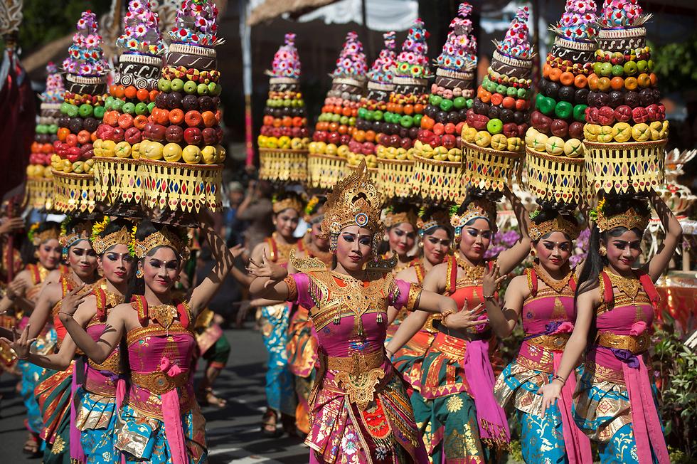 רקדניות בהופעה במהלך מצעד הפתיחה של פסטיבל אמנות בדנפסאר, באלי, שבאינדונזיה (צילום: רויטרס)
