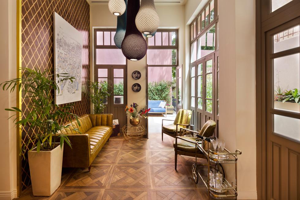 קירות הלובי כוסו ב''שטיח עץ'' בדוגמת מעויינים, שעשוי משני סוגי אלון. מהתקרה משתלשל מקבץ מנורות סרוגות של המעצב אריאל צוקרמן (צילום: אסף פינצ'וק)