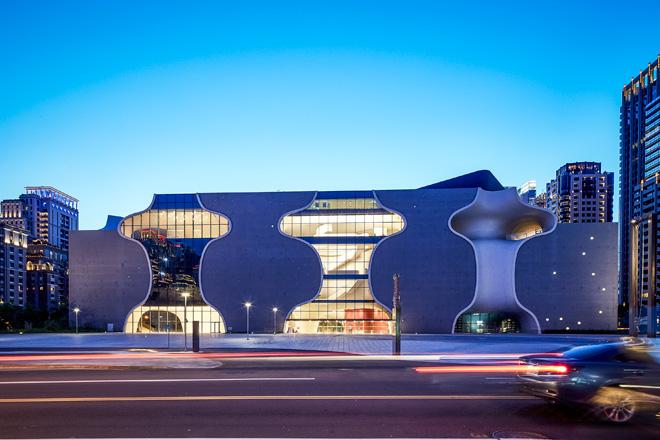 החזית המוארת בערב. קימורים שקופים ואטומים, שילוב של בטון וזכוכית (צילום: National Taichung Theater)