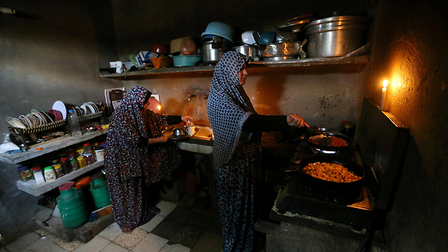 Women prepare dinner during power outage in Gaza (Photo: Reuters)