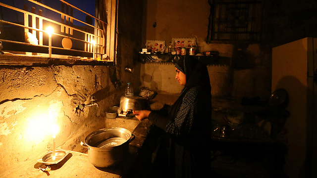 Mujer de Gaza lavando los platos a la luz de las velas debido a un apagón (Foto: Reuters)