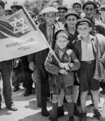 Little Lolek Yisrael Lau (holding a flag) with his brother Naftali (on the left )and other children from Buchenwald at the Atlit camp in July 1945 (photo courtesy of Yad Vashem Archive)
