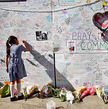 ילדה כותבת על קיר ברכות לנפגעי השריפה במגדל הלונדוני