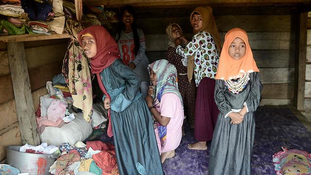 """בנות """"אורנג רימבה"""" שהתאסלמו. מדלקמות את הקוראן בהתלהבות (צילום: AFP) (צילום: AFP)"""