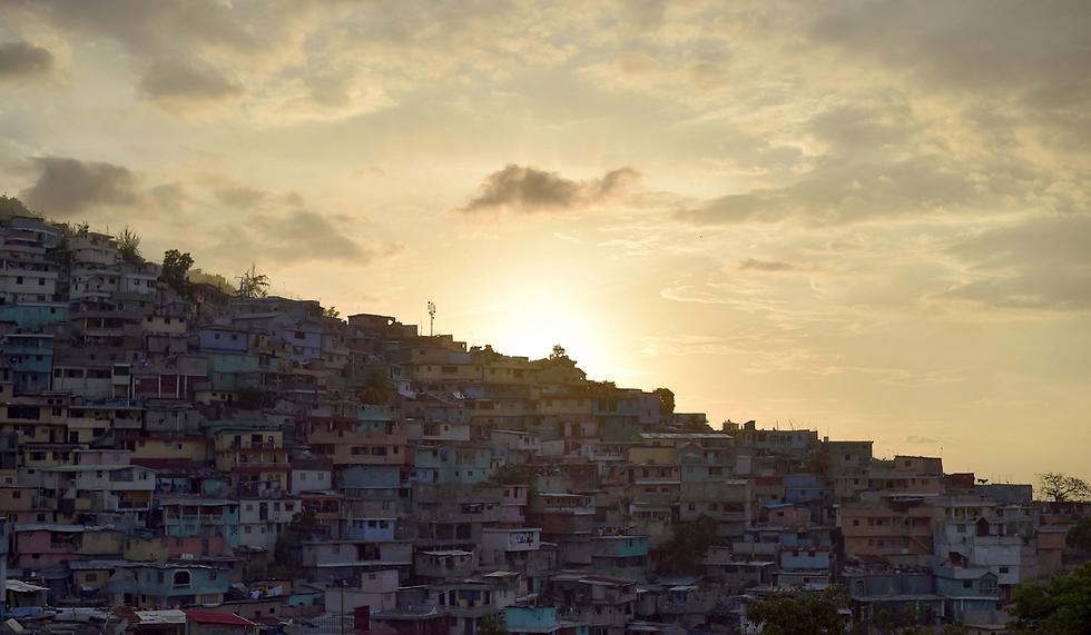 השמש שוקעת מעל שכונות הפחונים של פורט או פרינס, האיטי (צילום: AFP)
