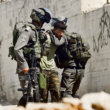 IDF fighters arrest a Palestinian during clashes near Ramallah, Saturday. The main challenge is to get through the Ramadan period by boosting preventing and intelligence activities (Photo: AP)