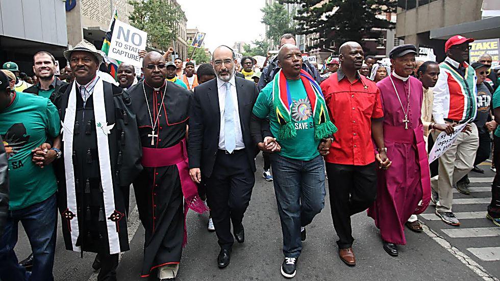 """בהפגנה נגד הנשיא של דרום אפריקה (זומה): """"היו חברים שחשבו שזה לא נכון להביע עמדה בנושא כזה, ושזה לא טוב לקהילה. אבל כרב, אני מרגיש שיש לי חובה מוסרית להשמיע קול"""""""