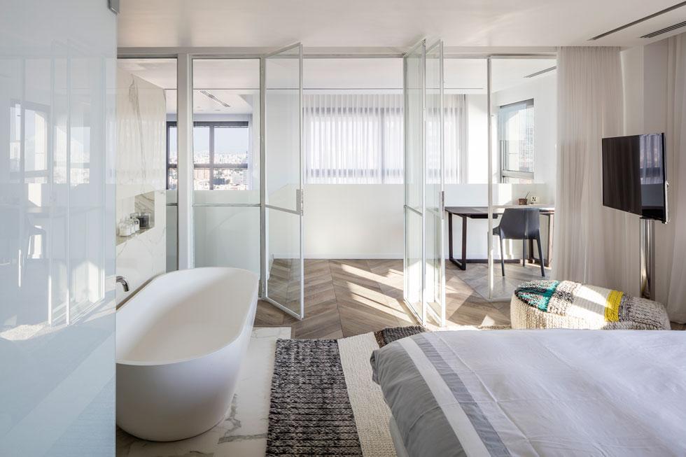 פינת העבודה מופרדת במחיצת זכוכית שקופה מאזור השינה. האמבטיה עומדת ליד המיטה (צילום: עמית גרון)