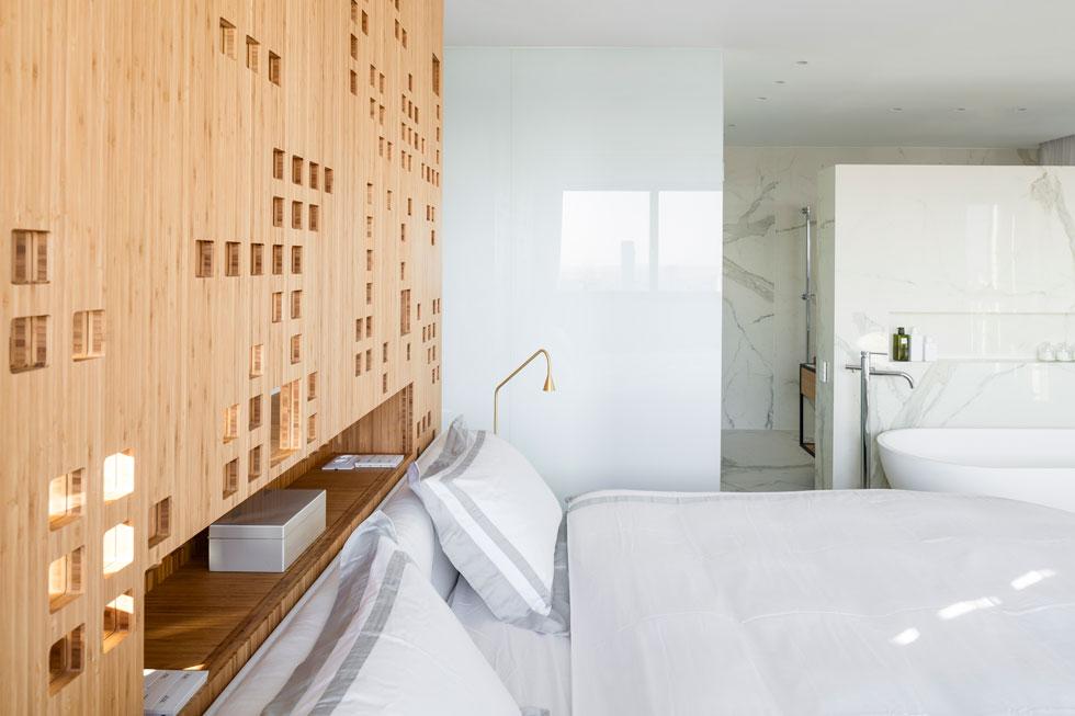 המיטה ניצבת במרכז חדר השינה ובגבה מחיצת עץ מחוררת. מאחורי המחיצה - חדר כושר, קיר נעליים וחדר ארונות (צילום: עמית גרון)