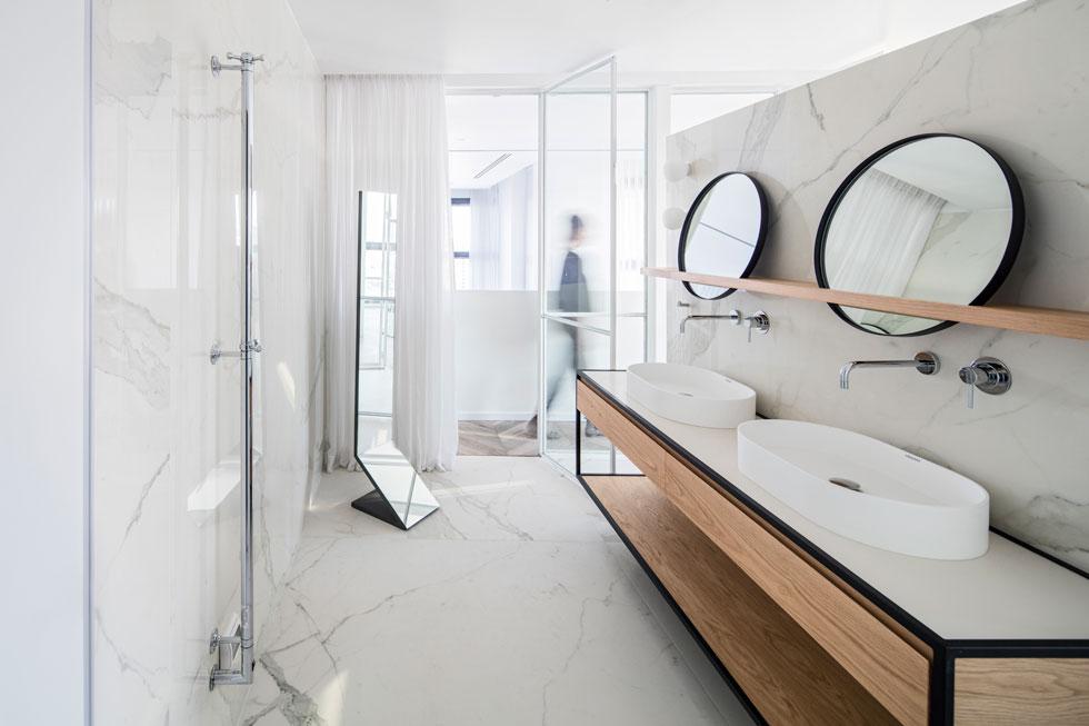 שני כיורי רחצה, מעבר לקיר, מוסתרים יותר, ובנוסף יש מקלחון זוגי ושירותים הסגורים בדלתות (צילום: עמית גרון)