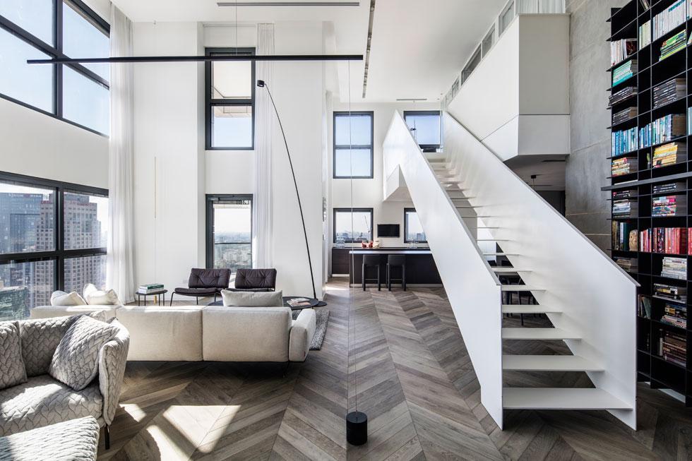 החלל המרכזי בדירה, ששטחה הכולל 215 מטרים רבועים. גרם המדרגות הדומיננטי מושך את המבט למעלה, אל קומת הגלריה, שבה סוויטת השינה של בני הזוג. הדירה נקנתה כמעטפת ריקה: ''נכנסנו והרגשנו כמו בבית פרטי תלוי באוויר'', אומרת בעלת הדירה. ''דבר לא חוסם ואף אחד לא יכול לראות אותנו'' (צילום: עמית גרון)
