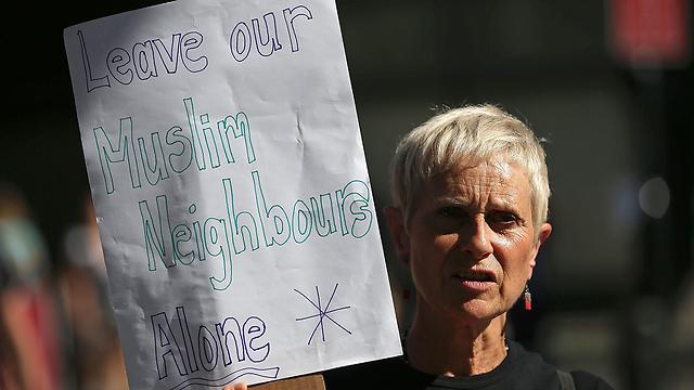 """""""פאשיסטים ואיסלאמיסטים רוצים אותו הדבר"""". מחאה של אישה אחת (צילום: AFP)"""