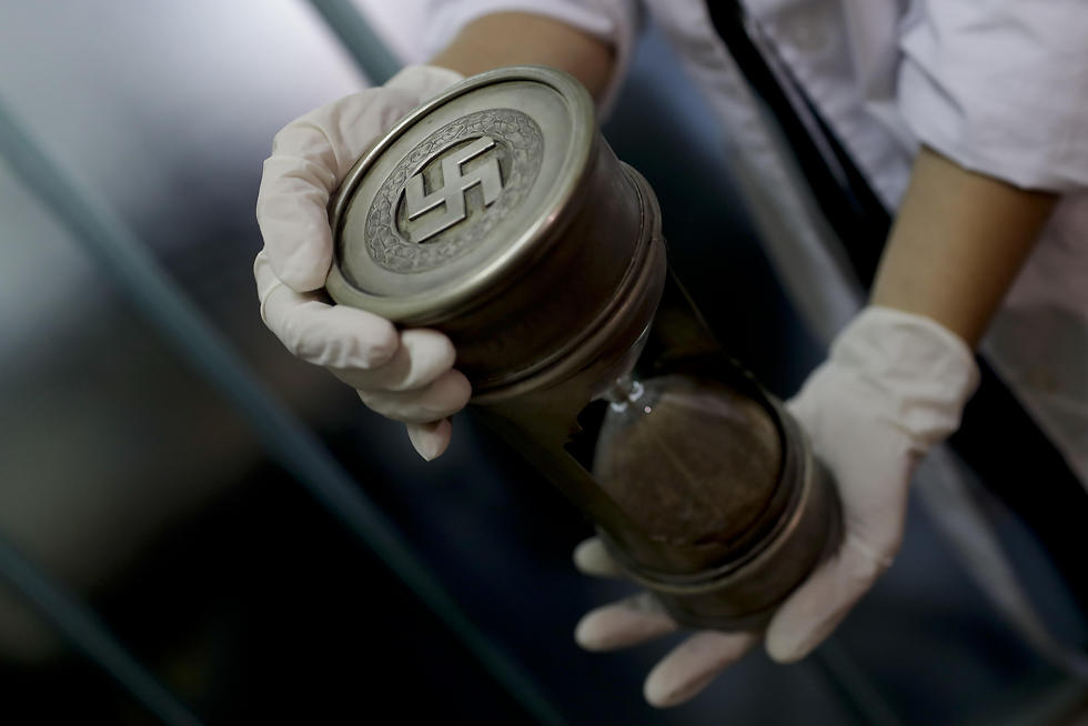 A member of the federal police holds an hourglass with Nazi markings at the Interpol headquarters in Buenos Aires, Argentina (Photo: AP) (Photo: AP)