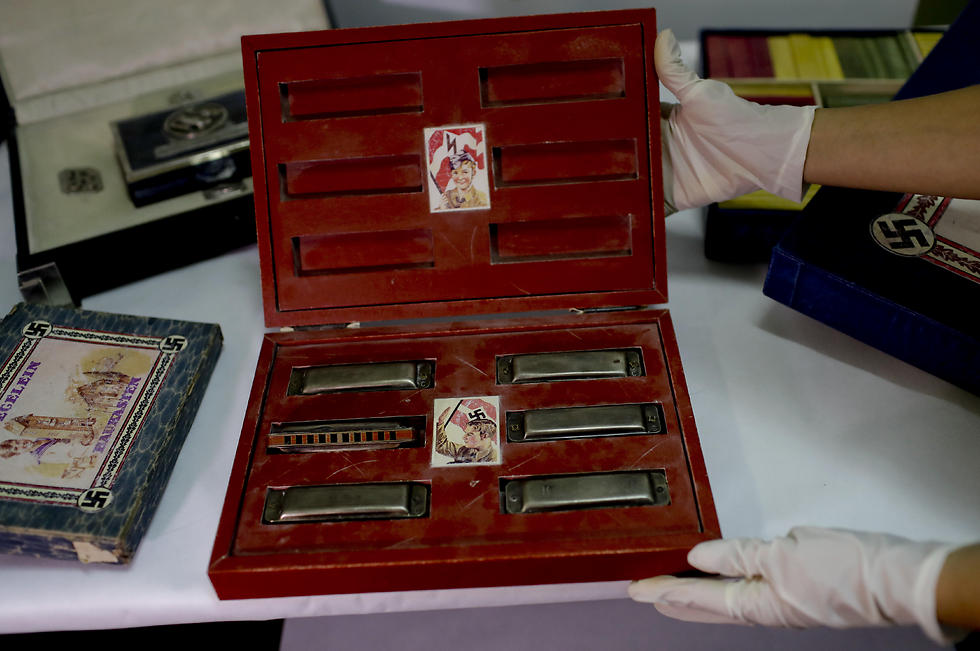 A member of the federal police shows a box with swastikas containing harmonicas for children at the Interpol headquarters in Buenos Aires (Photo: AP) (Photo: AP)