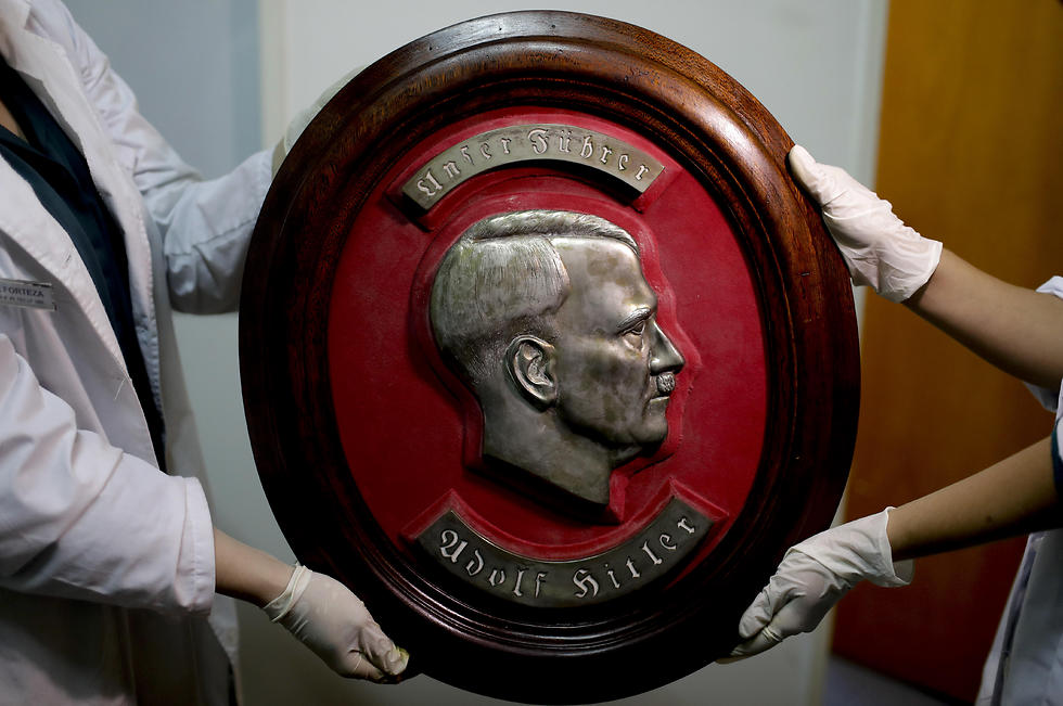Members of the federal police show a bust relief portrait of Nazi leader Adolf Hitler at the Interpol headquarters in Buenos Aires (Photo: AP) (Photo: AP)
