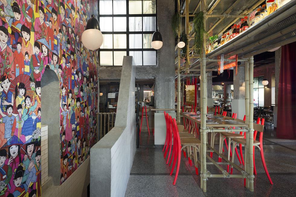 הצבעוניות עזה. רגלי הכסאות צבועים באדום-ניאון ועל קיר המדרגות היורדות למרתף איור גדול של וייטנאמים בלבוש מסורתי (צילום: גדעון לוין)