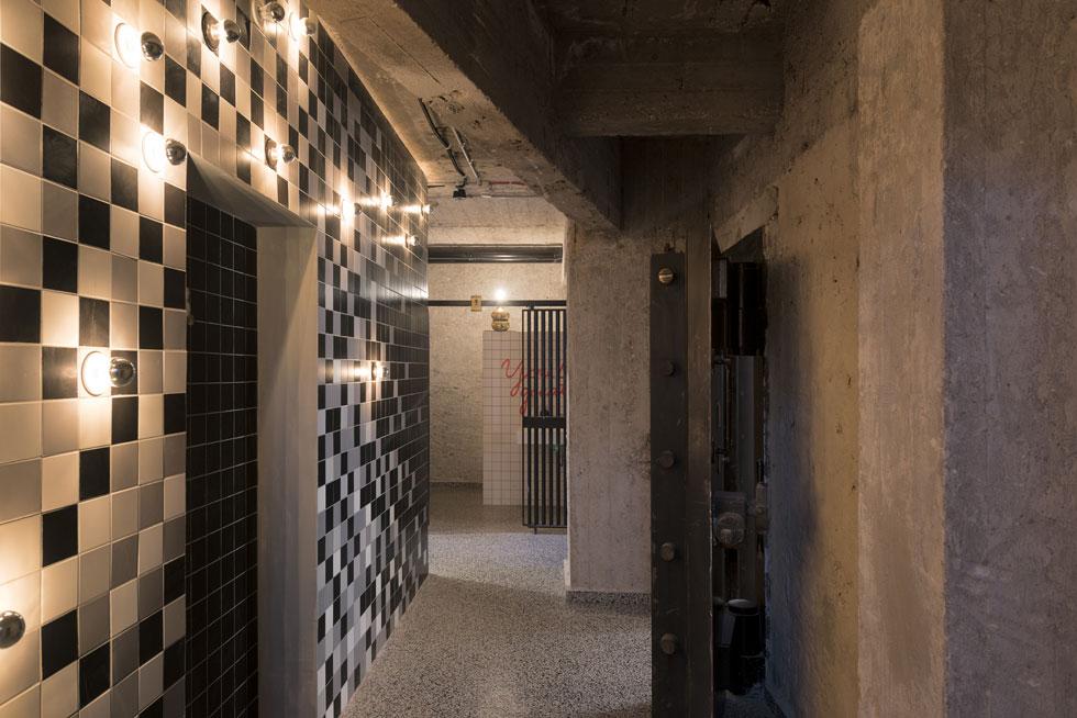 בקומת המרתף שירותים (ומתוכנן גם בר). כאן האלמנט היחיד שנשמר מהבנק - דלתות הכספות הכבדות. סקלת הצבעים הותאמה להן: קירות בטון חשוף, אריחים בשחור-אפור-לבן ונורות לבנות, עגולות (צילום: גדעון לוין)