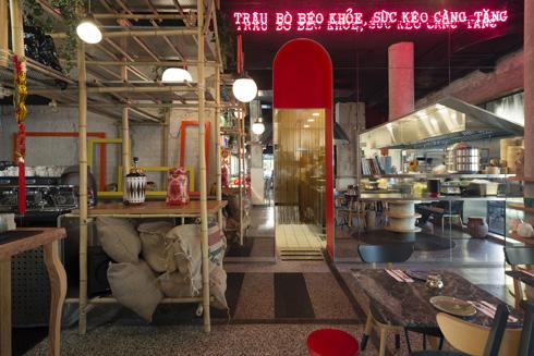 אווירת רחוב עם כתובות ניאון, מדפי במבוק וכניסה למטבח שמודגשת במסך של חוטים אדומים (צילום: גדעון לוין)