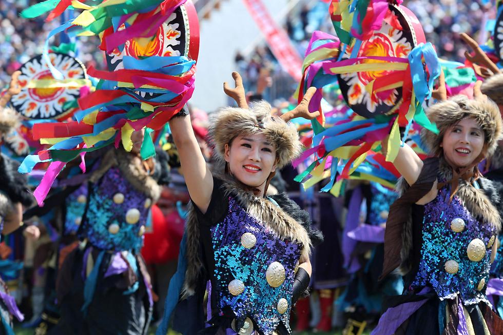בנות המיעוט האתני הז'ה רוקדות בפסטיבל בצפון-מזרח סין (צילום: AFP)