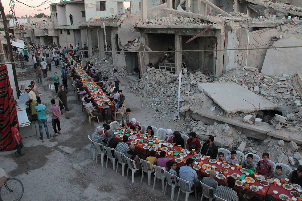 ארוחת השבירה של צום הרמדאן ליד מבנים הרוסים בדומא, בפרברי דמשק, סוריה (צילום: AFP)