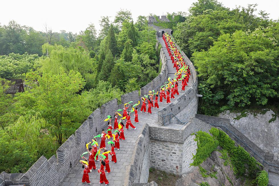 תלמידים מופיעים עם תופים בחומה הסינית (צילום: רויטרס)