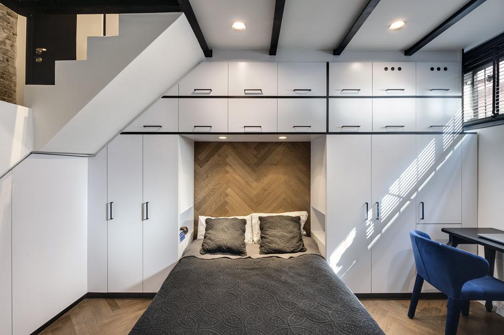 למטה זהו ארון בגדים שעוטף את המיטה. גב המיטה כוסה בפרקט, כמו הרצפה, ומתחת למדרגות ארון שסוגר על מכונות הכביסה והייבוש (צילום: עודד סמדר)