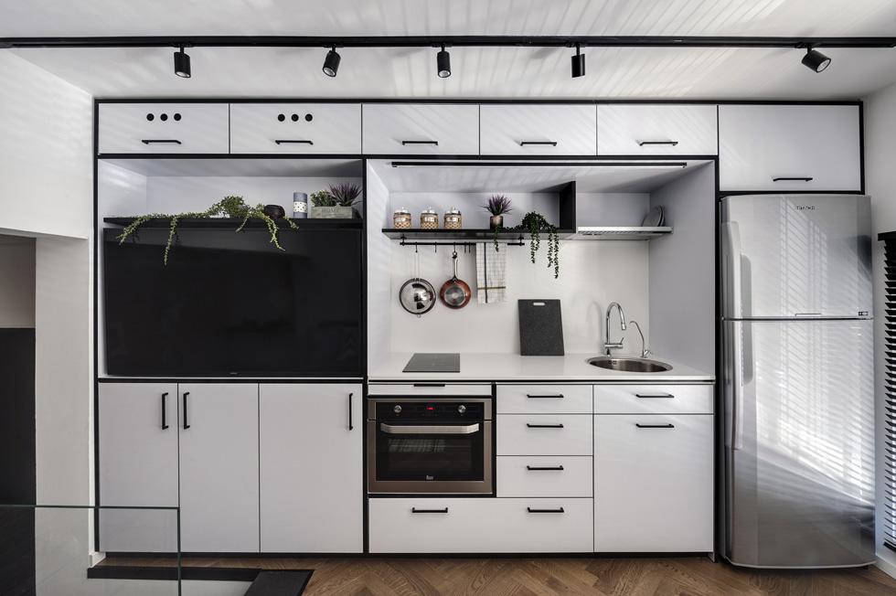 אלמנט מרכזי ובולט הוא קיר ארונות פורמייקה שנבנה לגובה כל הדירה. למעלה הוא מכיל מטבח, מסך טלוויזיה ומערכות מדיה (צילום: עודד סמדר)