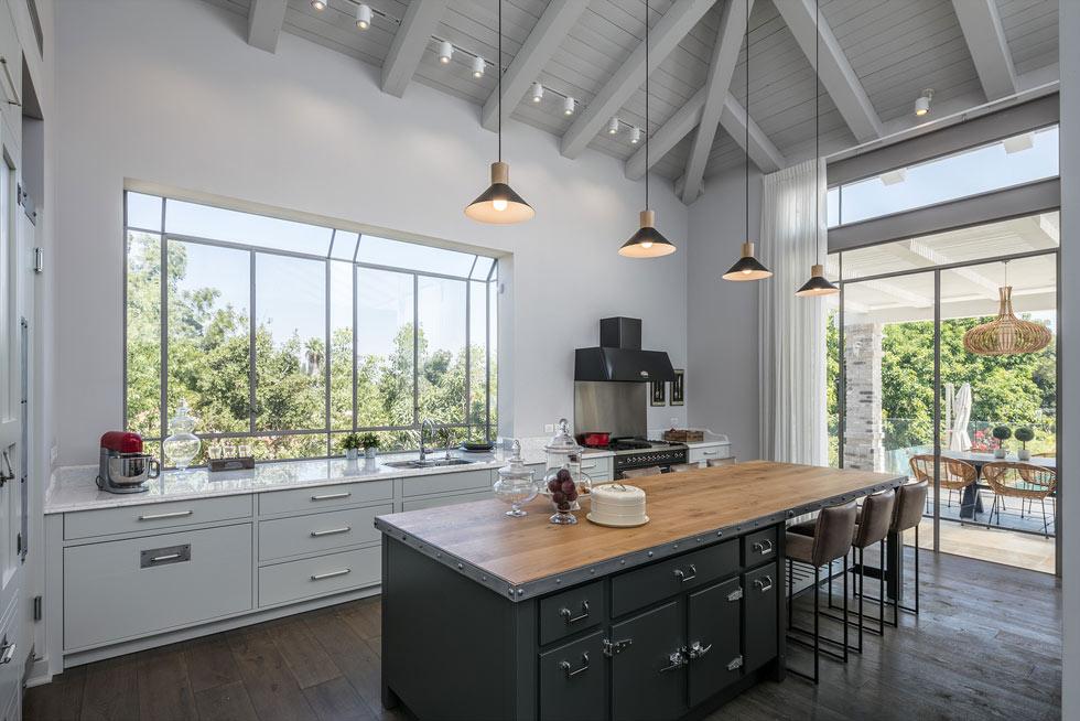 במרכז המטבח אי שמזכיר מקררים תעשייתיים. אור טבעי חודר מבעד החלונות הרבים (צילום: עוזי פורת)