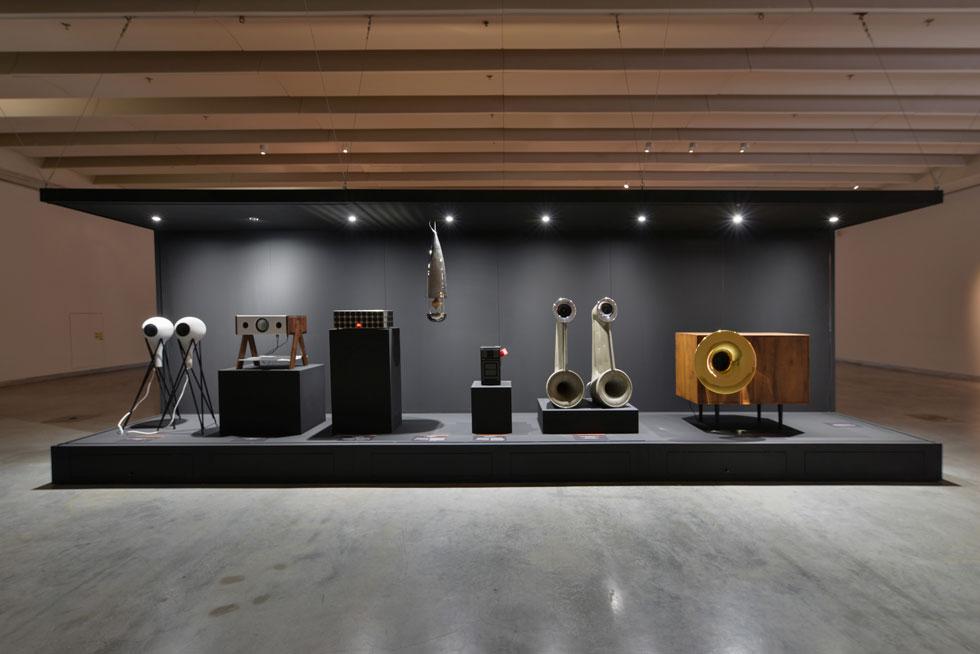 בכניסה לגלריה במה  שעליה שבעה רמקולים ייחודיים בעיצובם, שמשמיעים יצירה מקורית שכתבו מתן דסקל ושלו נאמן. כל אחד מהרמקולים משמיע קבוצת כלים אחרת, וכדי להאזין ליצירה כדאי לקחת כמה צעדים אחורה (ולהשתדל לבוא בשעות שקטות של המוזיאון, שכן האקוסטיקה כאן היא אויבו של הסאונד) (צילום: שי בן אפרים)