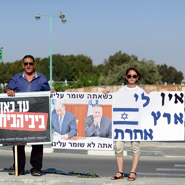 Simcha Latman (R) and Tamir Hajaj with the signs. 'There are Likud voters who have had enough too' (Photo: Haim Hornstein)