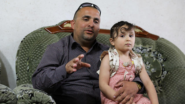 Palestinian Mahmoud Awissat, who drives a school bus for Israeli children, holds his daughter during an interview with Reuters. (Photo: Reuters)