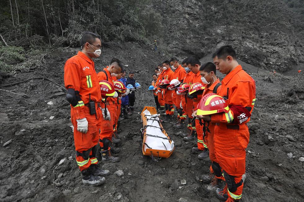 אנשי הצלה במחווה שקטה לפני פינוי גופה מאתר מפולת בשינמו, סין (צילום: רויטרס)