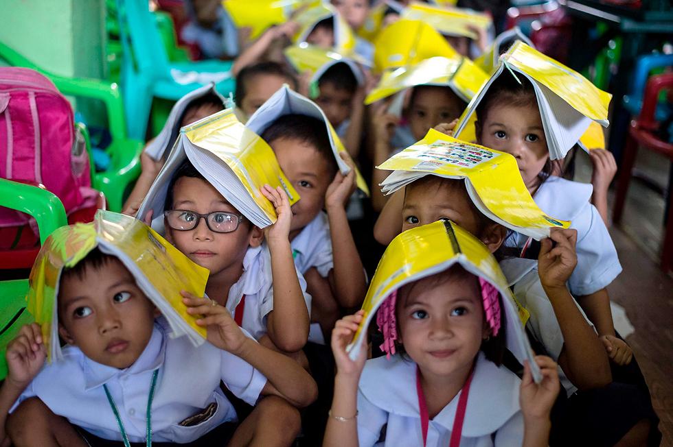 תרגיל התגוננות לשעת אסון בבית ספר יסודי במנילה, הפיליפינים (צילום: AFP)