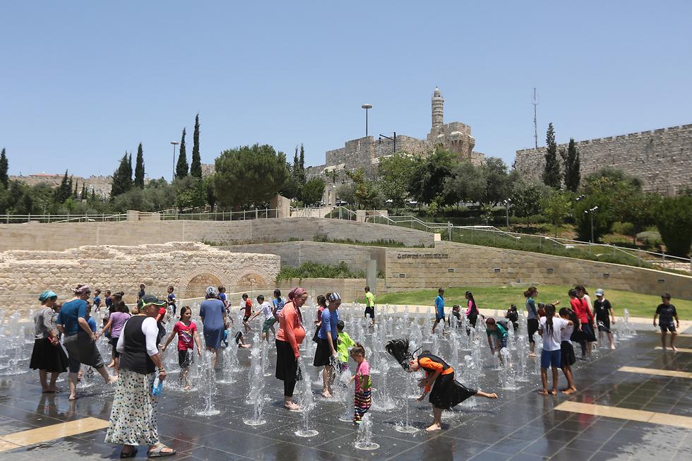 ילדים משתכשכים במים במזרקה בירושלים (צילום: גיל יוחנן) (צילום: גיל יוחנן)