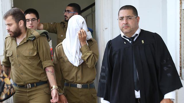 החייל החשוד באונס (פניו מכוסות) בבית הדין הצבאי (צילום: צביקה טישלר)
