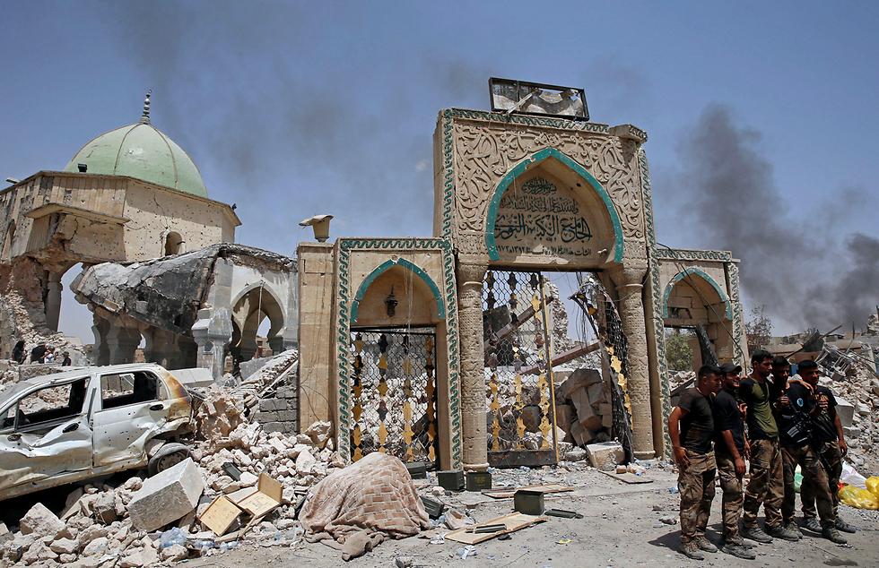כוחות ביטחון עיראקיים ליד הריסות מסגד אל-נור במוסול, שנהרס על ידי אנשי דאעש. באותו מסגד הכריז בעבר מנהיג דאעש, אבו בכר אל-בגדדי על הקמת החליפות האיסלאמית שבראשותו (צילום: רויטרס)