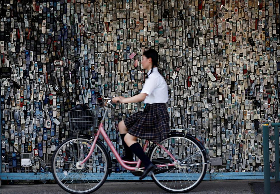 נערה חולפת עם אופניה ליד קיר חנות שמצופה בטלפונים ניידים שאסף הבעלים שלה במשך 20 שנה. טוקיו, יפן (צילום: רויטרס)