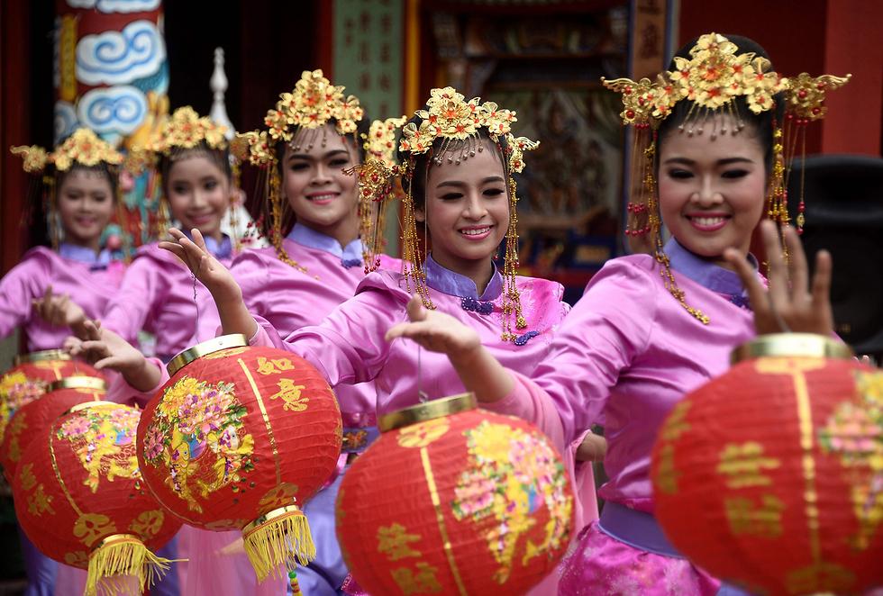 נשים תאיות רוקדות בלבוש מסורתי בחגיגות יום הולדת 102 למקדש הסיני קואו לינג ג'י במחוז נאראתיוואט (צילום: AFP)