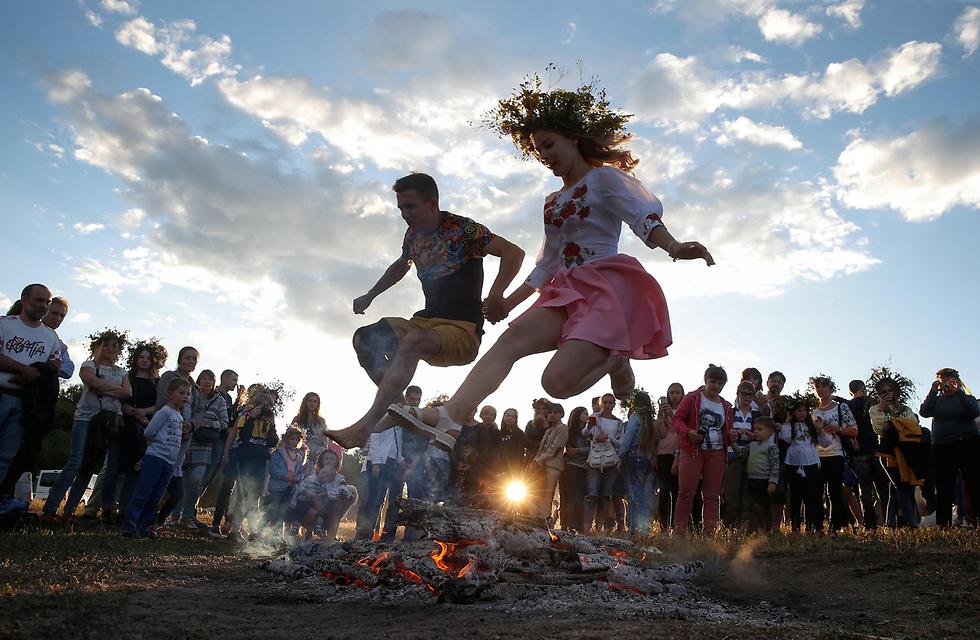 צעירים קופצים מעל אש במהלך פסטיבל איוון קופאלה בקייב, אוקראינה, שמסמן את תחילת הקיץ (צילום: EPA) (צילום: EPA)