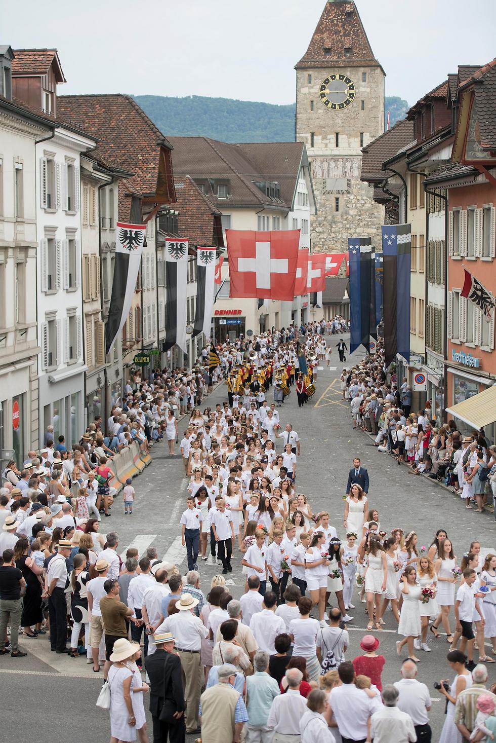 """חגיגות """"מיינצוג"""" לילדים ובני נוער בארגאו, אחד מהקנטונים הצפוניים של שווייץ. האירוע שנערך זה יותר מ-400 שנה נערך מדי שנה ביום שישי הראשון של חודש יולי (צילום: EPA)"""