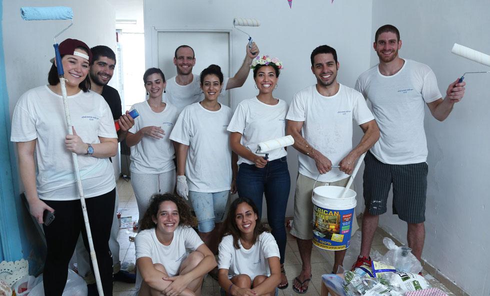 """ביטון (במרכז) עם החברים שהשתתפו בשיפוץ. """"אנשים מכל הארץ עזרו לי: אחד תרם צבע, אחר קנה חומרי ניקוי"""" (צילום: צביקה טישלר)"""