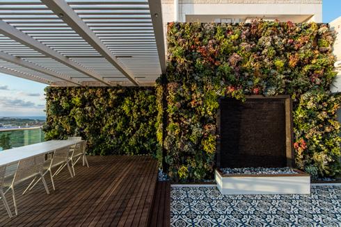 מרפסת הסלון עם קיר צמחייה, מפל מים ופינת אוכל חיצונית (צילום: עמית גרון)
