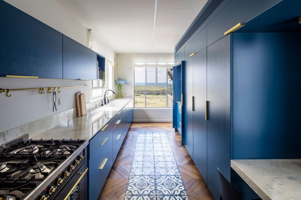 המטבח בנוי כשני פסים מקבילים של ארונות כחולים. בארונות הגבוהים (מימין) מקרר אינטגרלי ומשטח נסתר למכשירי חשמל קטנים. משמאל: פס של ארונות נמוכים ותלויים. בעלי הבית ביקשו מטבח שלא יהיה פתוח לגמרי למרחב הציבורי. לפני השיפוץ היה כאן קיר הטלוויזיה של הסלון (צילום: עמית גרון)