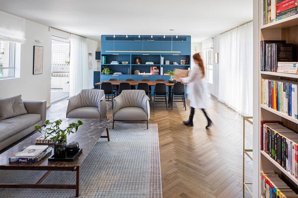 מבט מהמסדרון, שלאורכו ארון גדול וספרייה. ספרייה כחולה מגדירה את פינת האוכל, ומצדה השני המטבח (צילום: עמית גרון)