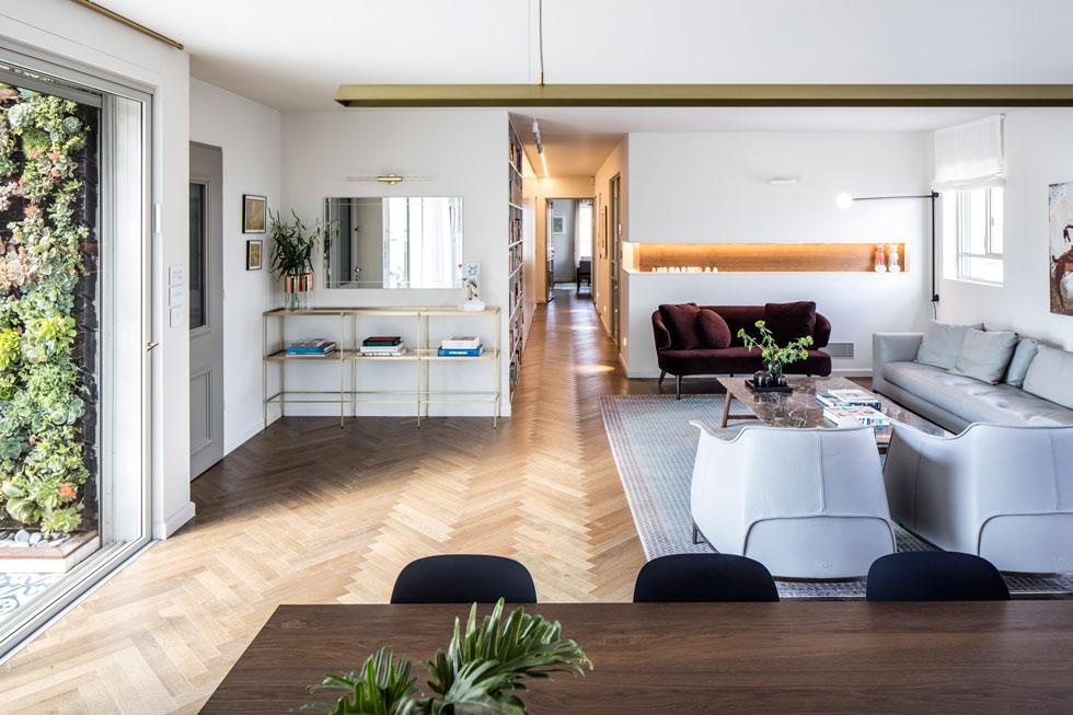 """מבט מפינת האוכל לעומק הדירה. המסדרון מוביל אל החלקים הפרטיים, שבהם חדר שינה, חדר עבודה, חדר טלוויזיה וממ""""ד המשמש לאירוח הנכדים (צילום: עמית גרון)"""