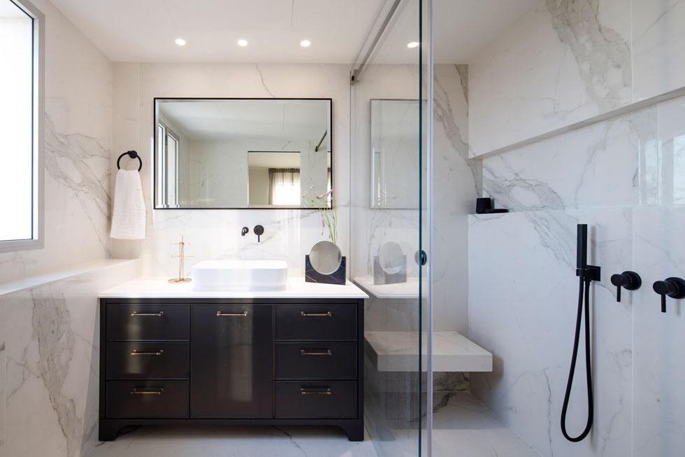 בחדרי הרחצה רצפה וקירות שיש, ארונות כיור בסגנון קלאסי ואבזור שחור (צילום: עמית גרון)
