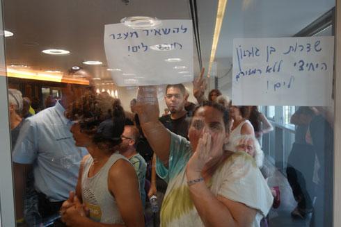 התושבים מפגינים מבעד לקיר הזכוכית. לא הורשו להיכנס עם שלטים (צילום: מיכאל יעקובסון)