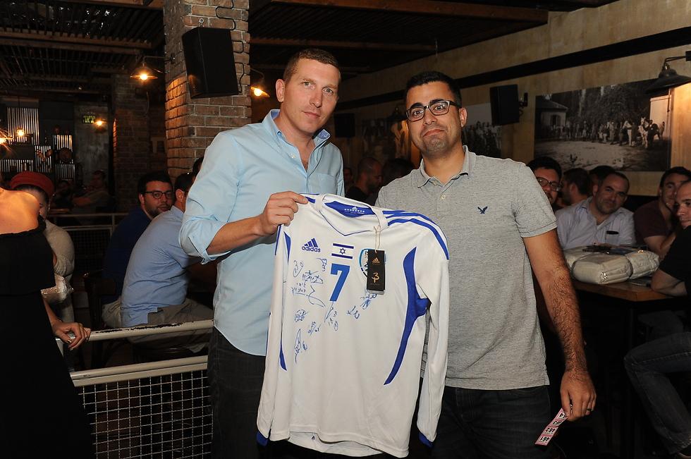 רפי מנדלסון (מימין) מקבל חולצה חתומה של נבחרת ישראל (צילום: איציק גדייב)