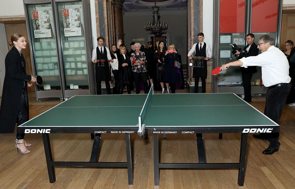 בהשקת החנות של סטיוארט ויצמן בלונדון, ג'יג'י חדיד משחקת טניס שולחן עם ויצמן, כשרגליה נטועות בזוג נעלי עקב